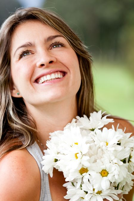 Happy woman smiling with a bunch of flowers