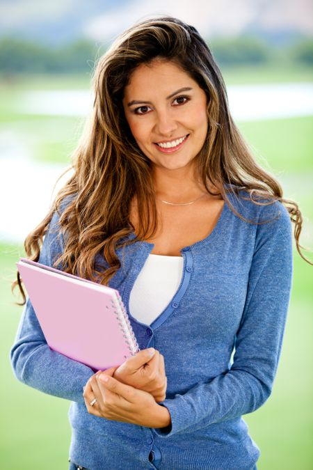Happy female student smiling and holding a notebook - outdoors