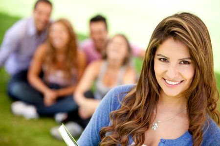 Female student smiling outdoors with a group of friends