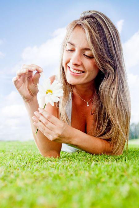 Romantic woman at the park detaching petals on a flower