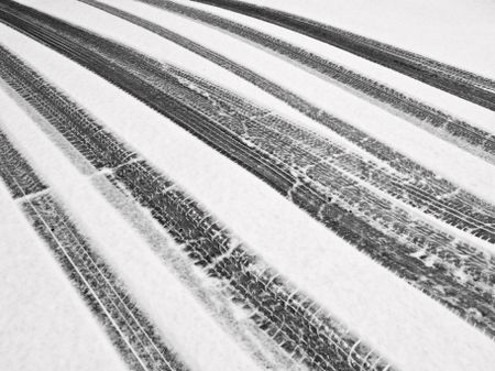 Winter at a glance, in black and white: Recent tire tracks through snow on ramp to garage