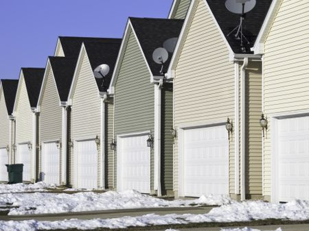 Building conformity: Row of nearly identical one-car garages in winter