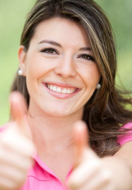 Girl with thumbs up expressing positivity - outdoors