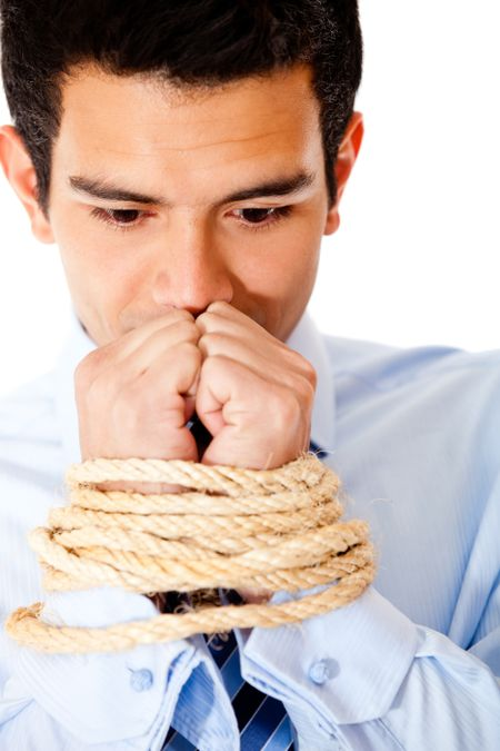 Businessman with hands tied  using a rope - isolated over a white backround