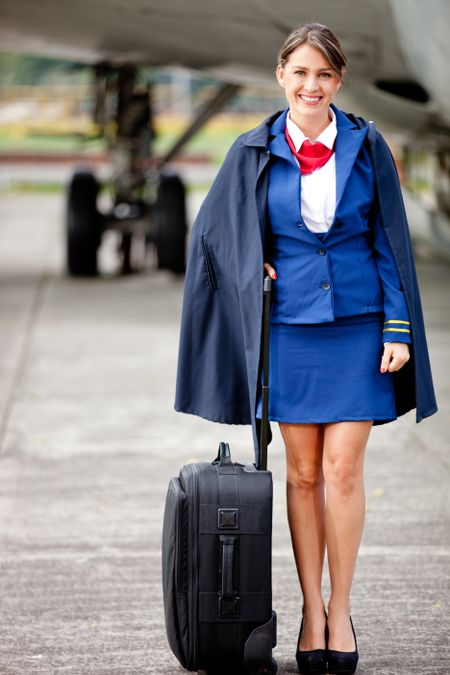 Beautiful flight attendant with her bag next to a aiplane