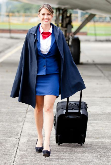Beautiful air stewardess walking next to an airplane with bag