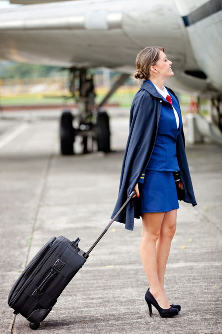 Beautiful air hostess with her bag next to an airplane