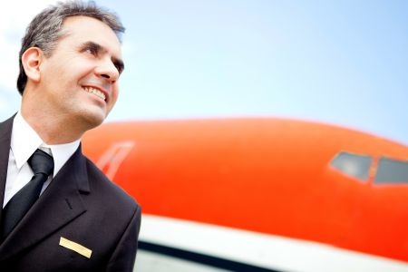 Portrait of a handsome pilot looking at the sky with an airplane at the background
