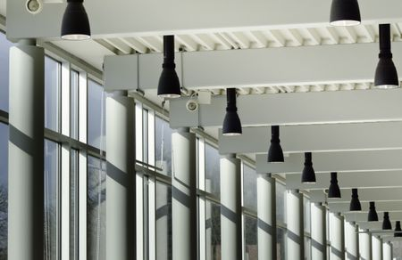 Architectural symmetry: Interior view of columns, windows, and light fixtures along hallway of state university
