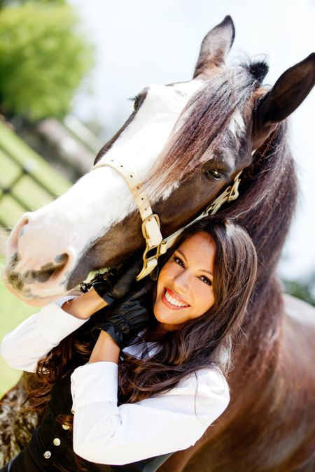 Portrait of a beautiful woman with a horse outdoors