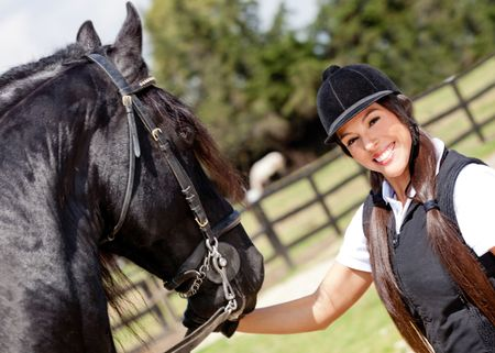 Woman with a beautiful black horse and smiling