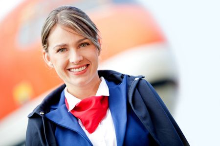 Beautiful air stewardess with a airplane at the background and smiling