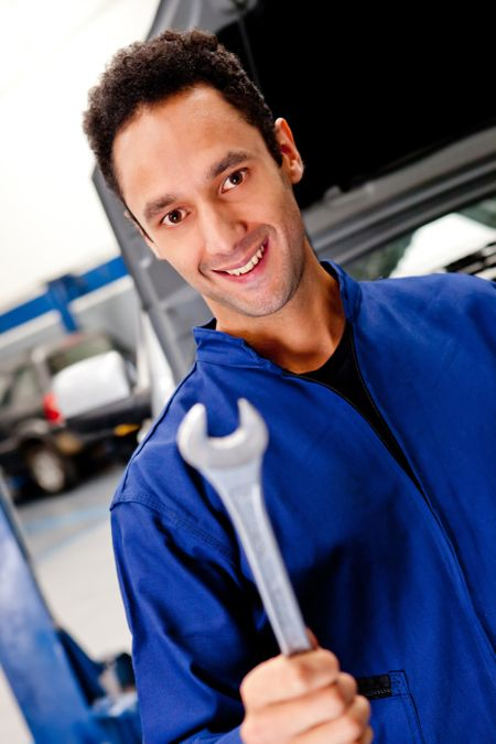 Male mechanic with a wrench at a car garage