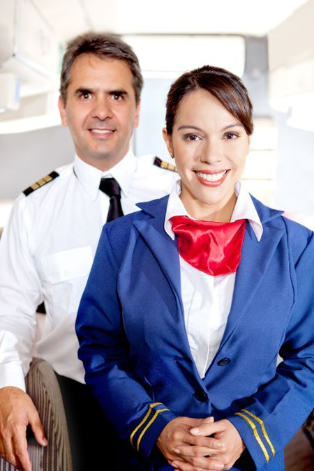 Pilot and air hostess in an airplane cabin smiling