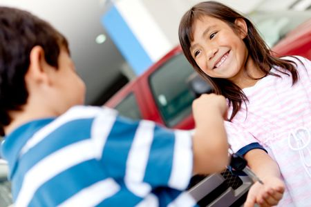 Happy kids playing with car keys at a dealership