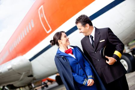 Pilot and flight attendant at the airport with an airplane at the background
