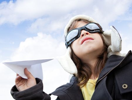 Young boy pilot holding a paper airplane looking at the sky