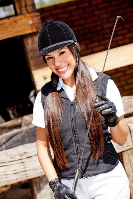 Beautiful female jockey in uniform with a whip