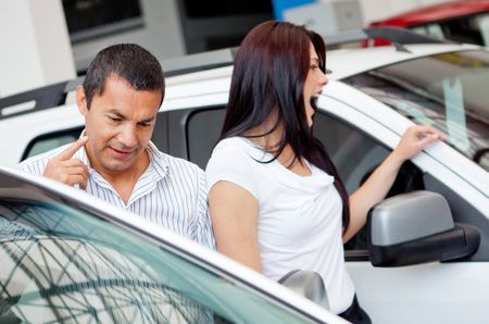 Couple at the dealer looking for a new car