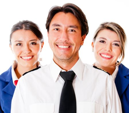 Pilot and flight attendants smiling �¢?? isolated over a white background