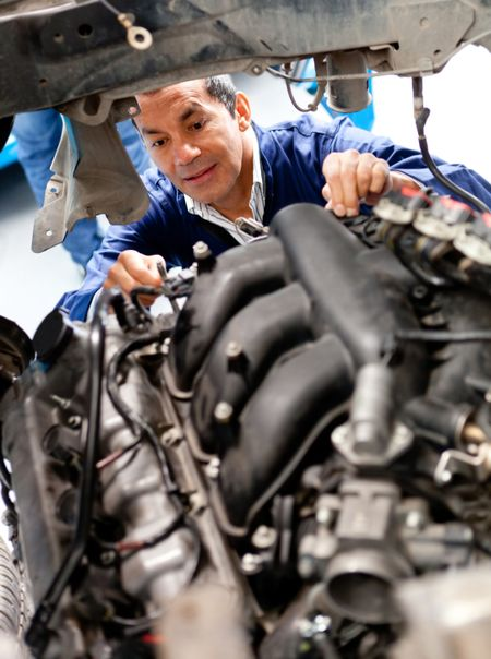 Male mechanic at a garage fixing a cars engine