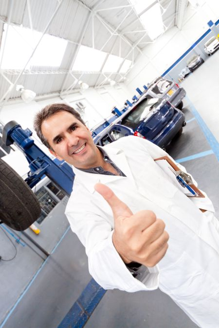 Male mechanic with thumbs up at a car garage