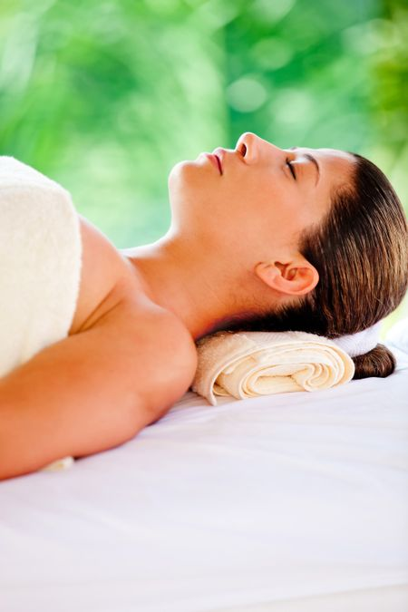 Beautiful woman lying down relaxing at a spa