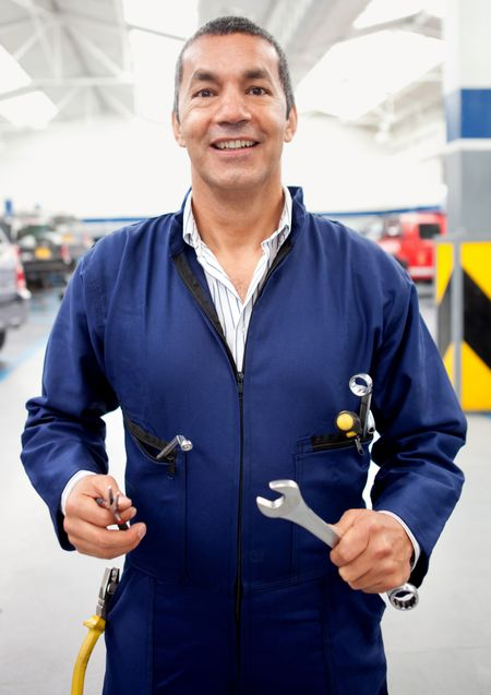 Male mechanic holding tools at a car garage and smiling