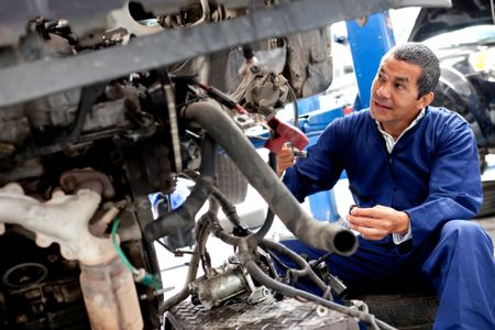 Male mechanic working on a car at a repair shop