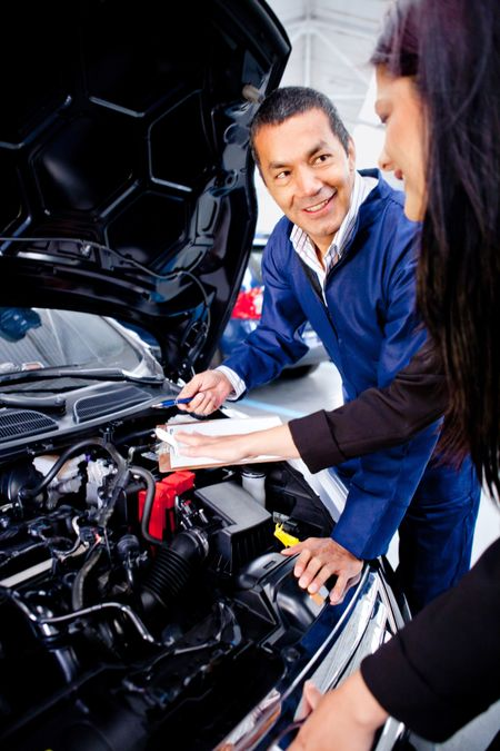 Mechanic explaining to a woman what is the problem with her car