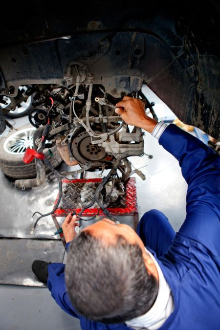 Mechanic at the repair shop fixing engine of a car