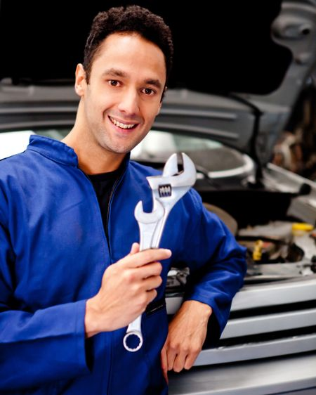 Mechanic working at a repair shop and holding tool