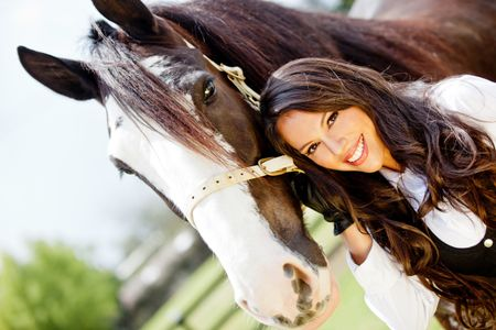 Beautiful woman portrait with a horse outdoors