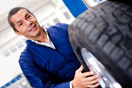 Mechanic changing car wheel at a repair shop