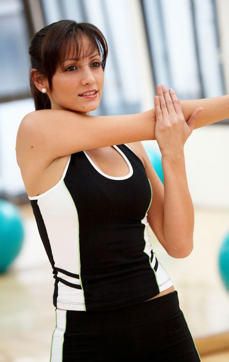 woman stretching out at the gym smiling