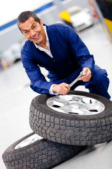 Male mechanic fixing car tire at the garage