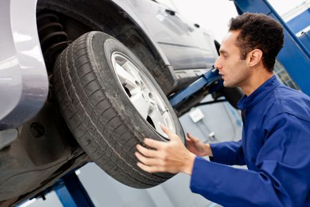 Mechanic repairing a car wheel at the garage