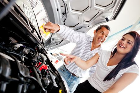 Couple buying a car and checking the engine