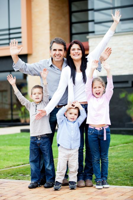 Happy family with arms up in front of a house