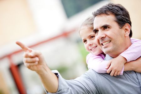Father and girl pointing away and smiling - outdoors