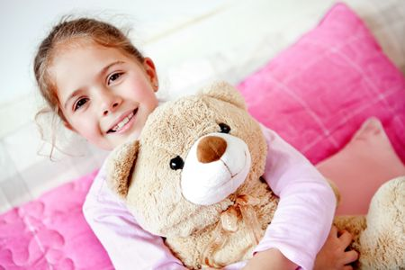 Little girl in bed hugging her teddy ber