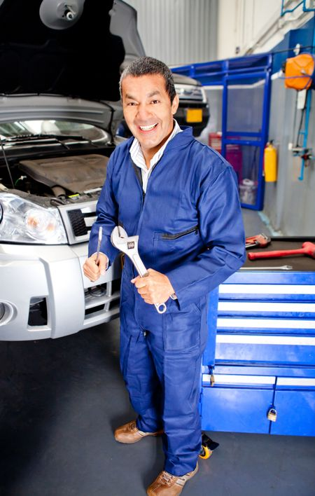 Car mechanic at an auto repair shop holding wrench