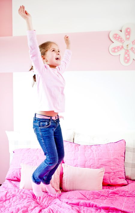 Happy little girl jumping on the bed