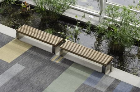 Pair of benches alongside long artificial pond inside convention center