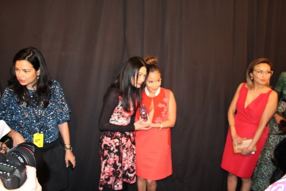 Vivienne Tam presents Adrienne Bailon with a gift backstage before the show.
