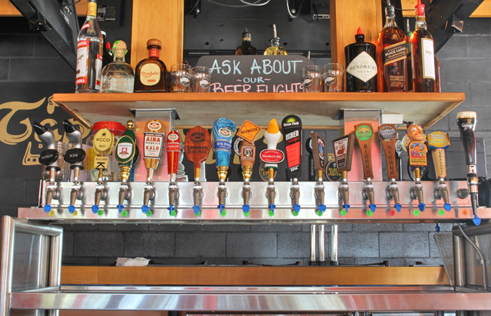 The bar is double-sided with tap handles running back to back. Beer prices range from $5 to $10.