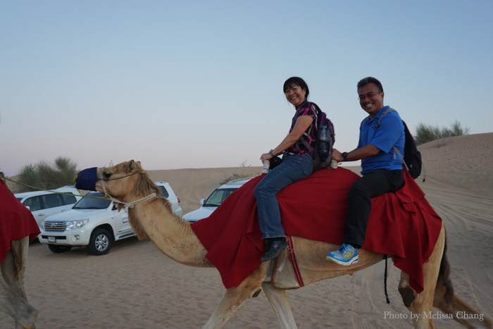 Val Ogi and Kyle Unten riding a camel.