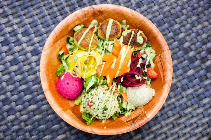 The Medi Bowl is an enormous bowl containing kalo falafel, fire-roasted baba ghanoush, beet hummus, and millet tabbouleh on a bed of greens drizzled with an herbaceous tahini sauce.