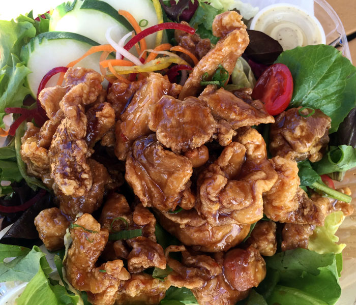 The garlic chicken salad comprises a fresh spring mix salad interspersed with cucumbers, tomatoes, rainbow curls, house dressing and savory, tender chicken morsels that are fried and tossed in a garlic-infused house sauce.