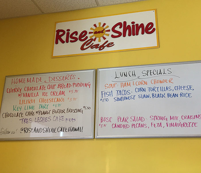 Homemade bakery items and daily specials are listed on a white board above the register.